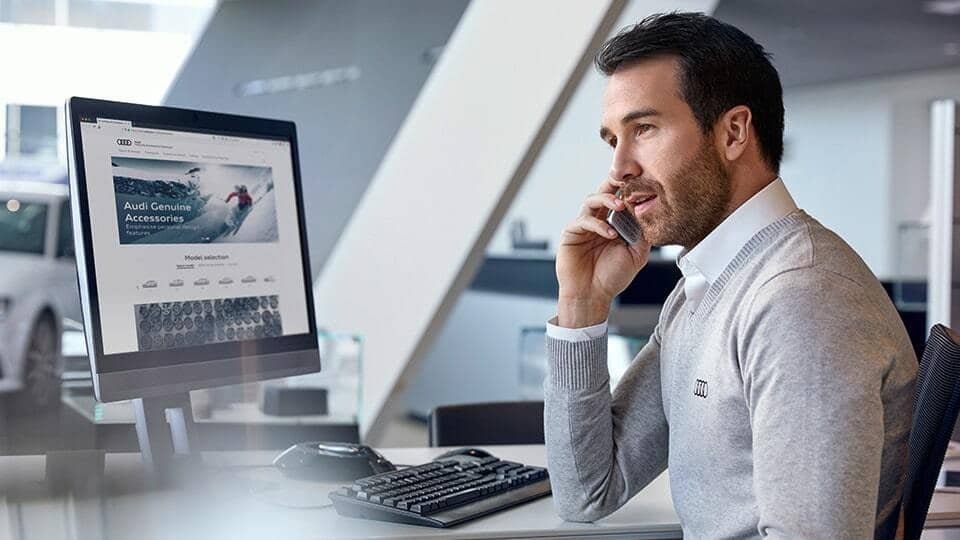 Man sitting a desk in front of a computer talking on the phone